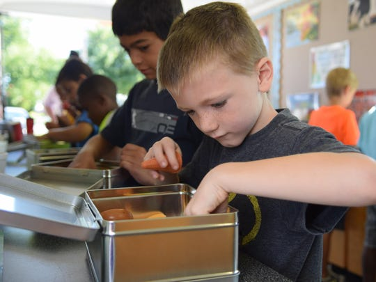 Robert Featherer looks through a lunch box filled with faux food items, picking out healthy choices in 2014. A recent study from Baylor University College of Medicine found lunches brought from home were even less nutritious than school lunches.