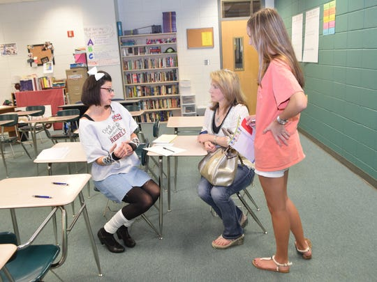 """Bonnie White (left), a gifted English teacher at Pineville High School, stepped out of the 1980s to talk with parent Darla Corley (second from right) and senior Sarah Corley on Tuesday. Pineville High School held a parents' night with a """"Back to the Future""""/1980s theme. The purpose of the night was to welcome parents and show them how to support their children."""