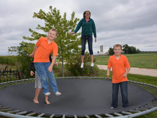 Matthew, Mariah Obry and Mitchell play on the trampoline at the farm.