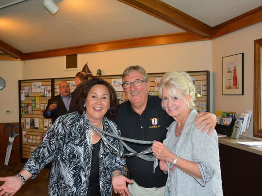 Wisconsin Tourism Secretary Stephanie Klett, left, shows off the scarf and jewelry provided to her by Tina Marie, right, whom Klett has known since Tina Marie outfitted her when she was Miss Wisconsin in 1992. Algoma Mayor Wayne Schmidt is in the center.