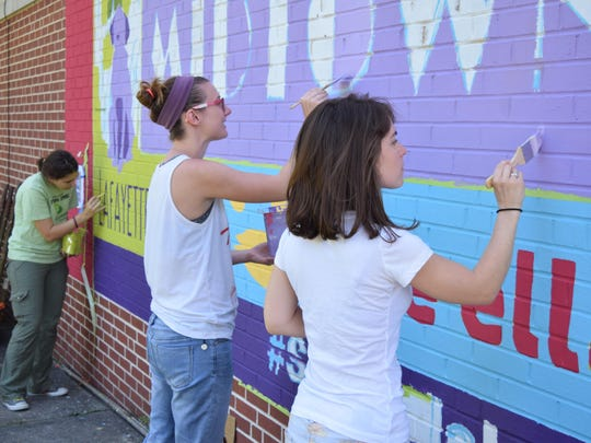 Maia Hannahs, Stefanie Kiedrowski and Alana Taylor (from left to right) paint parts of the Midtown mural.
