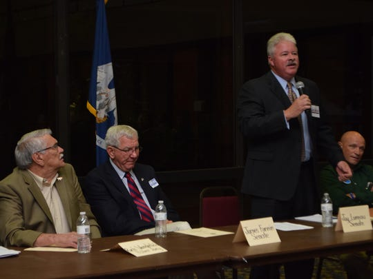 Jay Luneau (standing at right), a Senate District 29 candidate, answers a question at a candidate forum Thursday in Pineville.