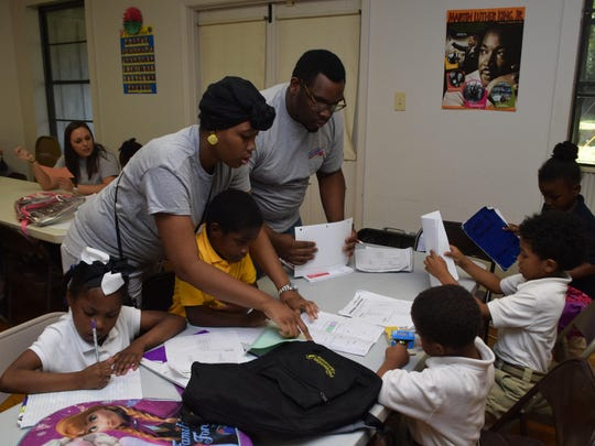 Student-workers Demetrius January (standing at right) and Autumn Gates (standing at left) help youngsters with their homework at the new after-school program at Fairway Terrace housing units. The program is among new recreational offerings being launched by the city of Alexandria.