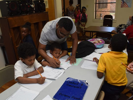 "Danrick O'Neail helps youngsters with their homework at the new after-school program at Fairway Terrace housing units in Alexandria. O'Neail, a student at LSUA, said he wants to help the children academically and ""teach them about life and guide them in the right way."""