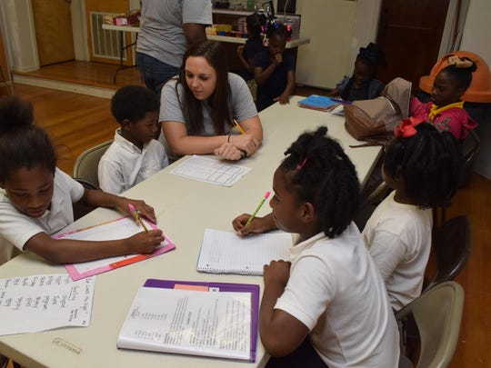 Chelsea Evans helps youngsters with their homework at the Alexandria Recreation Department's new after-school program at Fairway Terrace housing units.