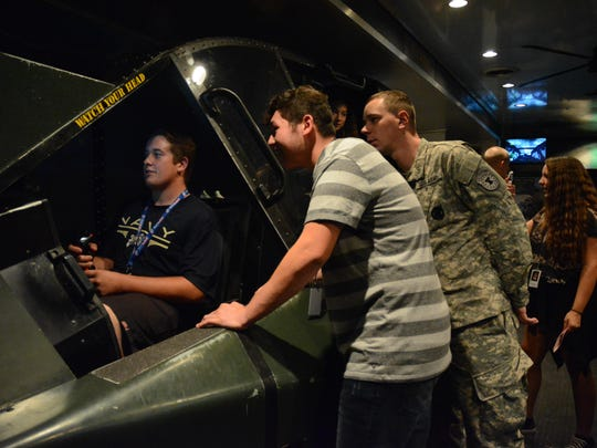 Students crowd around an Apache helicopter flight simulator in the U.S. Army's Aviation Adventure Semi-truck.