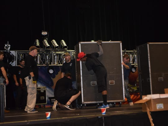 Stagehands roll cases into the stage at the Mari Center