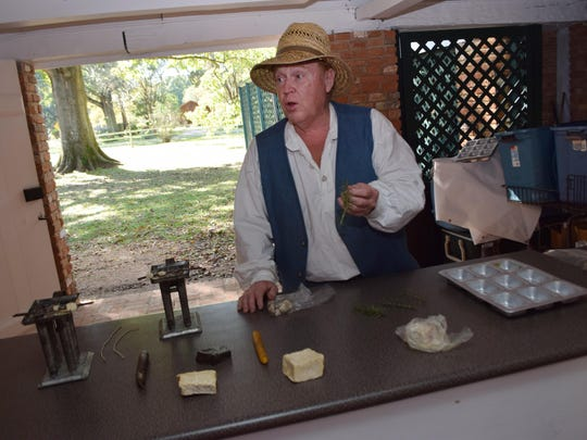 George Rogers, a volunteer and tour guide at Kent House, explains how candles and soap were made. The candles were made from bees wax and the soap from lye or lard.