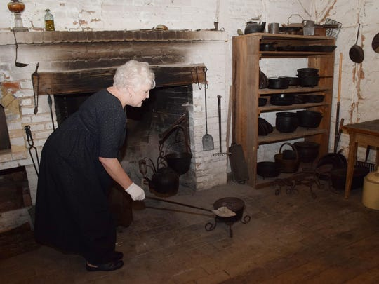 Sandy Lott, a part-time worker at Kent Plantation House, explains how meals were cooked in the open hearth kitchen by placing hot coals on the brick underneath the cast iron pots. Kent Plantation House offers a meal cooked entirely over the open hearth fro