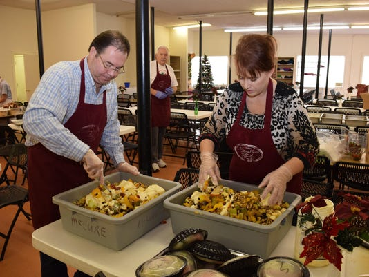Mark Roberts and his wife Tye Roberts mix fruit salad at the Manna House on Christmas Day. The Roberts were volunteering on Christmas Day. The Manna House, which serves meals to those in need, is run by the Diocese of Alexandria.