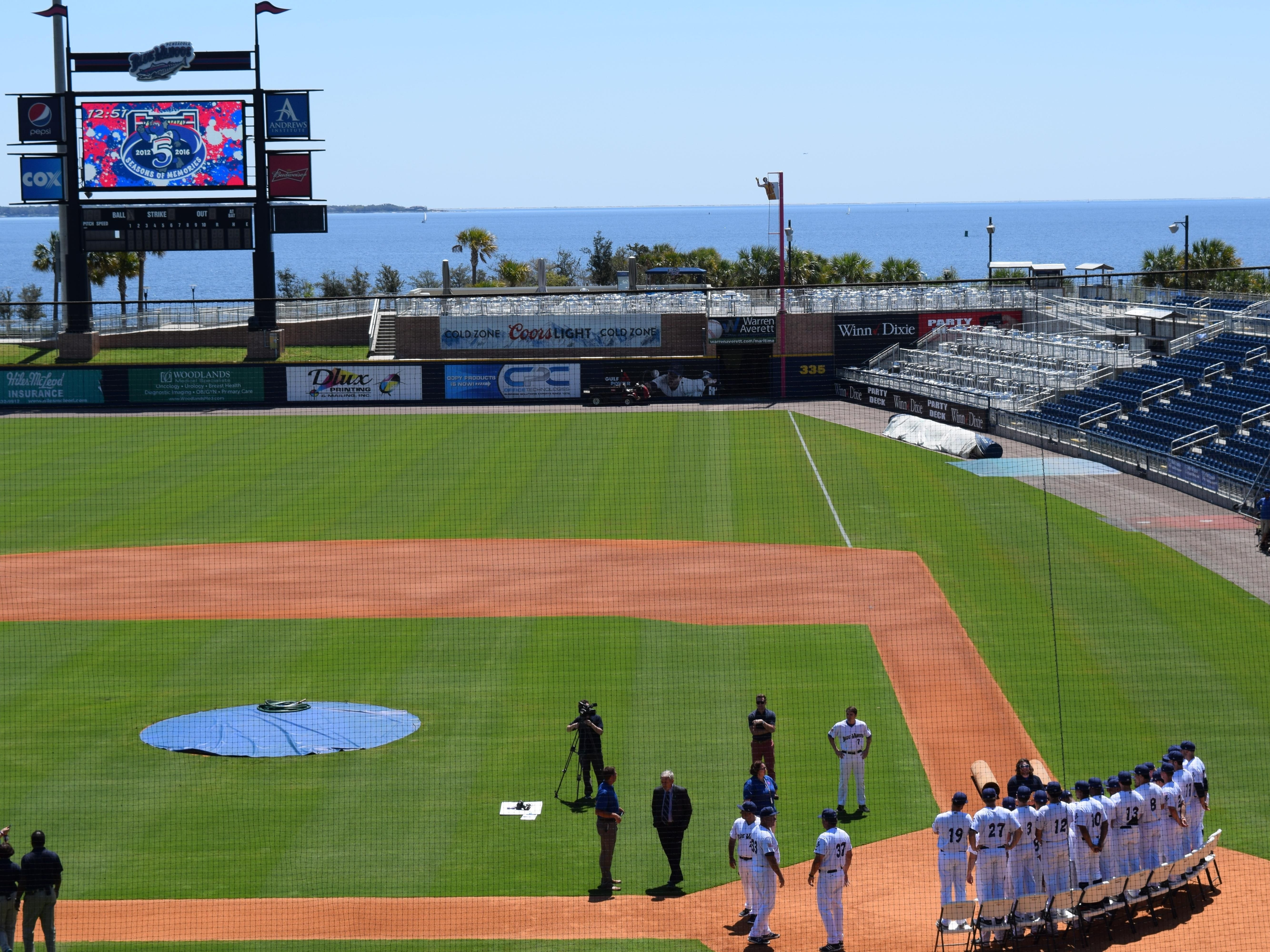 Amid spectacular backdrop, the Blue Wahoos players gathered on field to tape a sponsor commericial for season, prior their first practice Tuesday at Blue Wahoos Stadium.