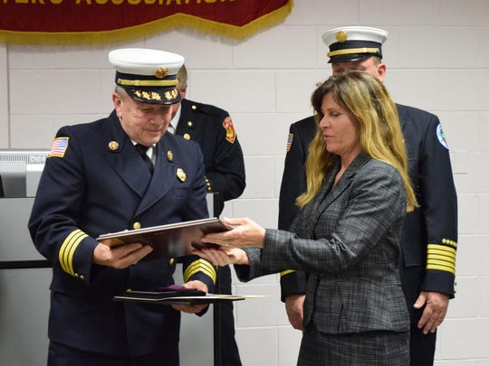 Robert H. Ade of the Egg Harbor City Fire Department receives an award from Egg Harbor City Mayor Lisa Jiampetti recognizing him for 50 years of service with the fire department.