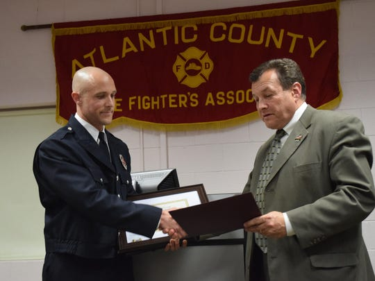 Capt. Scott Tilton of the Bayview Fire Comapny received a Meritorious Valor Award at the 25th annual Atlantic County Firefighters Association Valor Awards ceremony on April 20. He shakes hands with Atlantic County Freeholder John Risley.