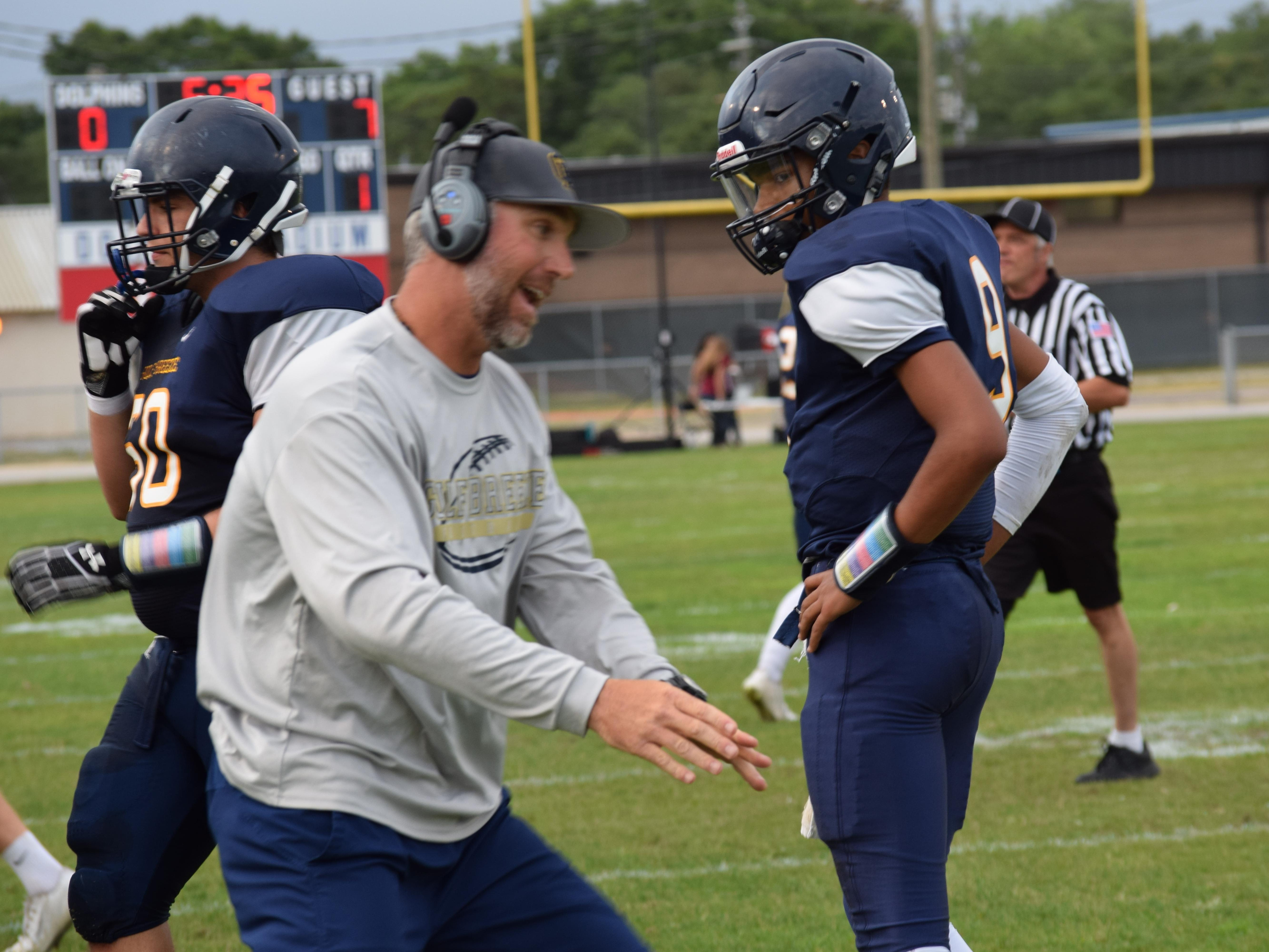 Gulf Breeze High coach Bobby Clayton talks with quarterback Daniel Brayton during the first half of Friday night's spring game at Dolphin Stadium.