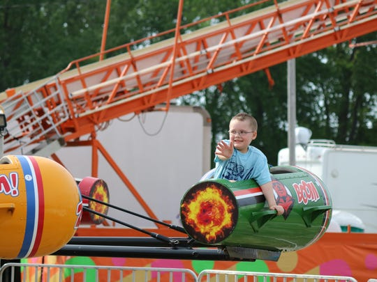 Noah Solis, 5, enjoyed a spin around in a rocket as the rides opened at last year's Walleye Festival in Port Clinton.