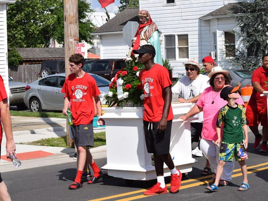 Saint Joseph High School students Joey Umosella, 16, of Hammonton and Marcellus Ross, 15, of Sicklerville, in front, and Louis Casadia, Maria Casadia and Vincenzo Marandino, 9, all of Hammonton, walk in the Feast Day procession.