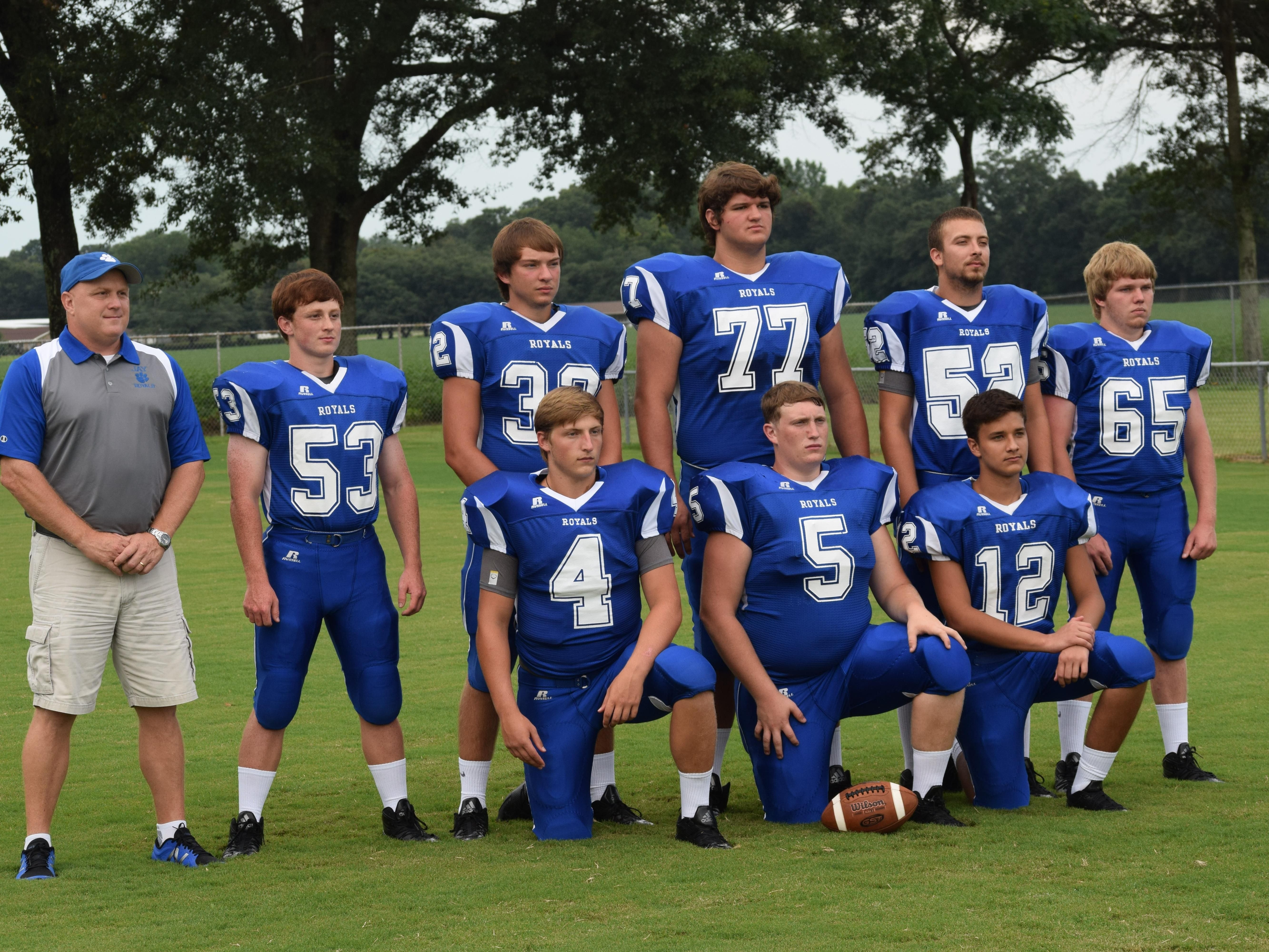 Jay High coach Melvin Kersey stands with his offensive group that includes senior leader Matthew Saylor (4) and mammoth tackle Cade Diamond (77) during team's picture day.