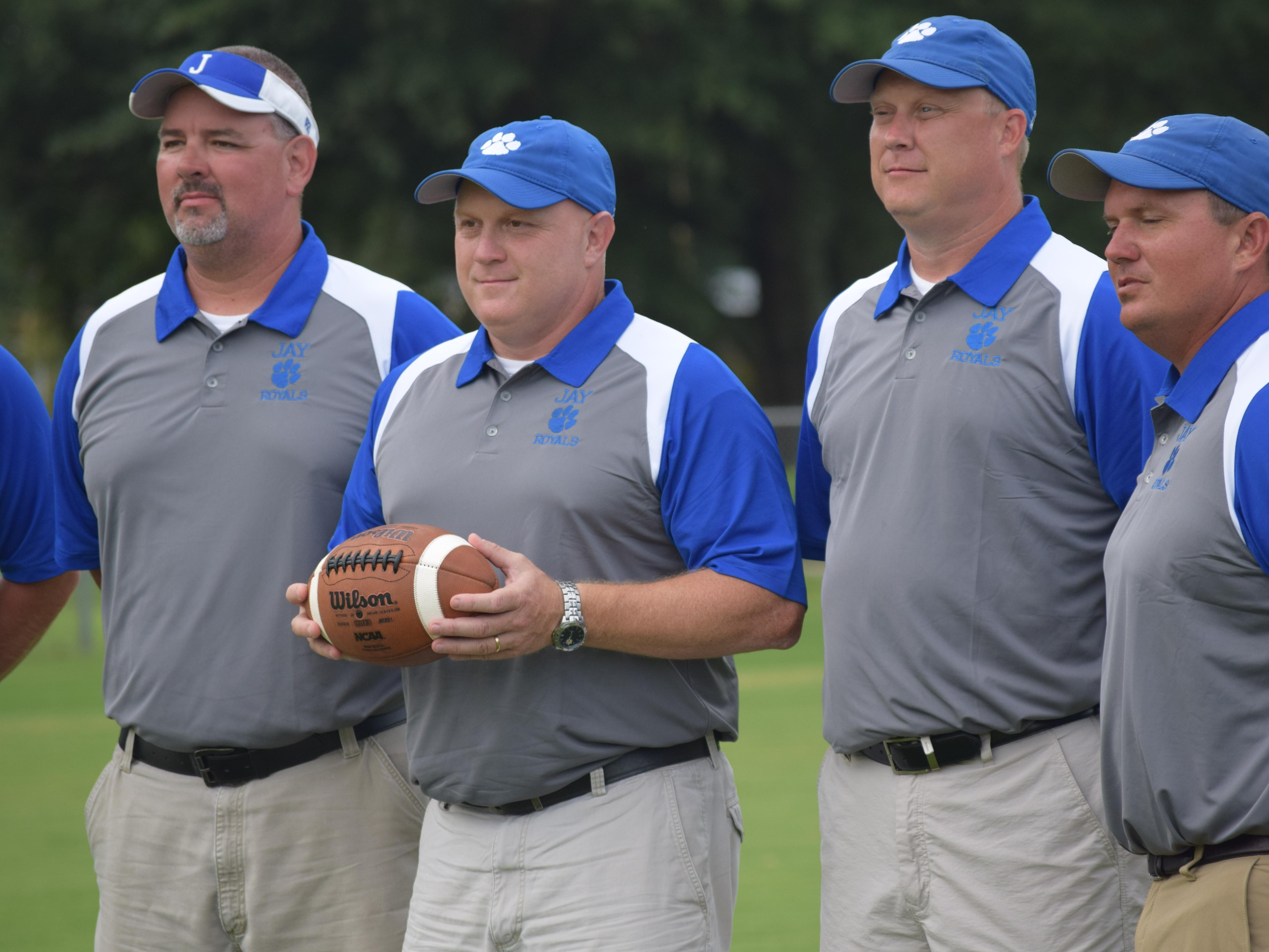 New Jay High football coach Melvin Kersey (holding football) with members of his coaching staff, including former teammates when they played at Jay in the 1990's.
