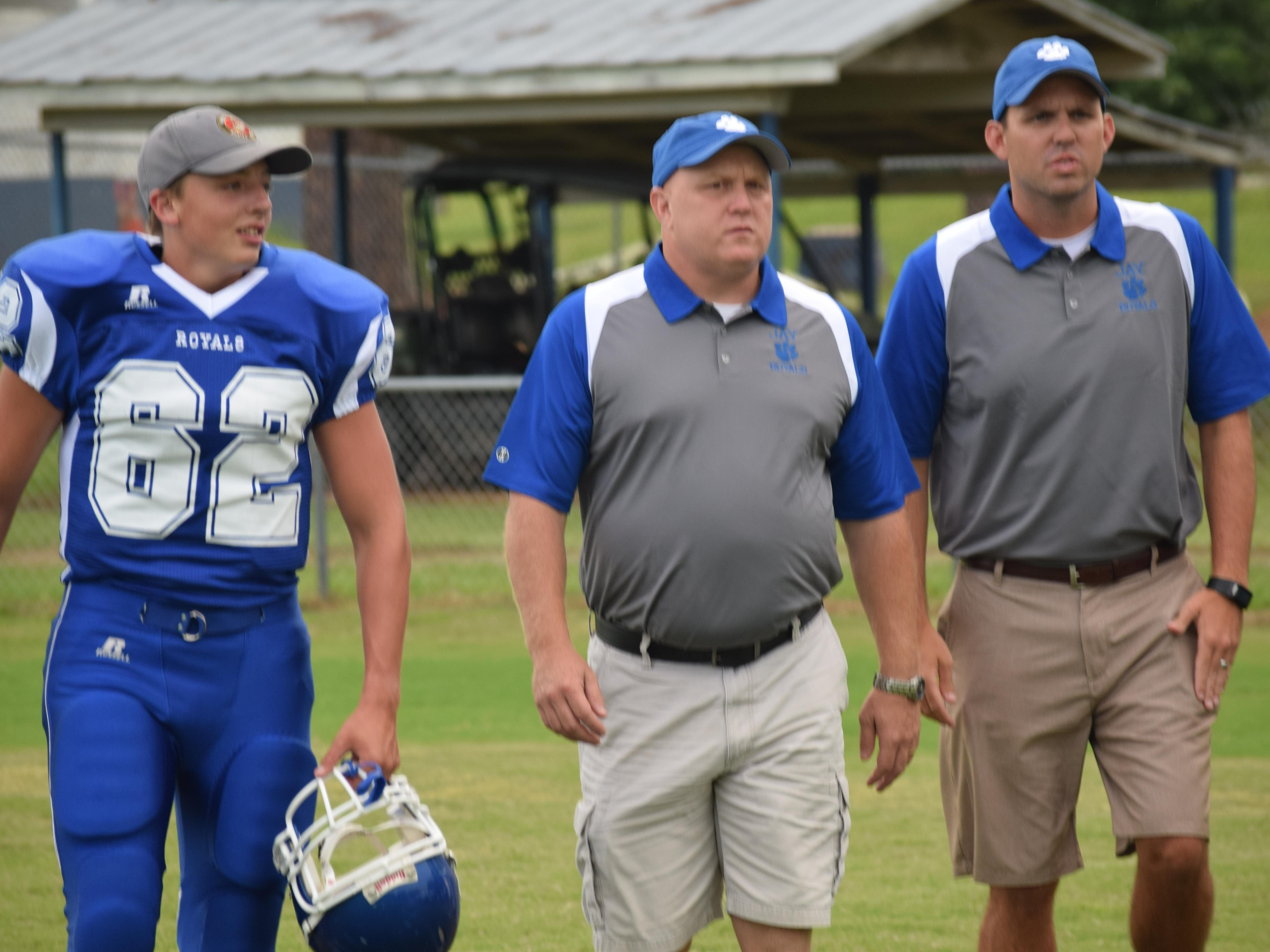 Jay head coach Melvin Kersey (center) and Brian Watson (right) were teammates on Jay football teams in the early 1990's. They head to field during team's photo day with Landon Smith