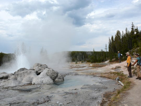 CDT Montana workers Norman Fortunate, Doug Bartholomew and Zuri Moreno pause to watch the Minute Man Geyser go off in the Shoshone Basis of Yellowstone National Park on Sept. 1.