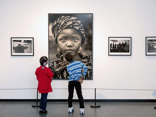 Art by Chester Higgins Jr. commands the interest of two children at the Sugar Hill Museum in Harlem.