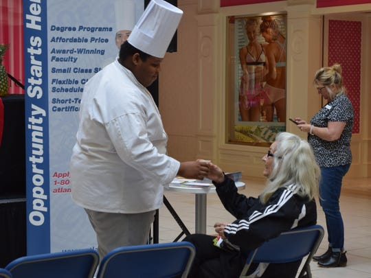 Academy of Culinary Arts student Mohammed Llabres of Vineland serves a sample of creamy white hot chocolate with ginger to Jamie Dougherty of Mays Landing during the Savory Saturdays cooking demonstration at the Hamilton Mall.