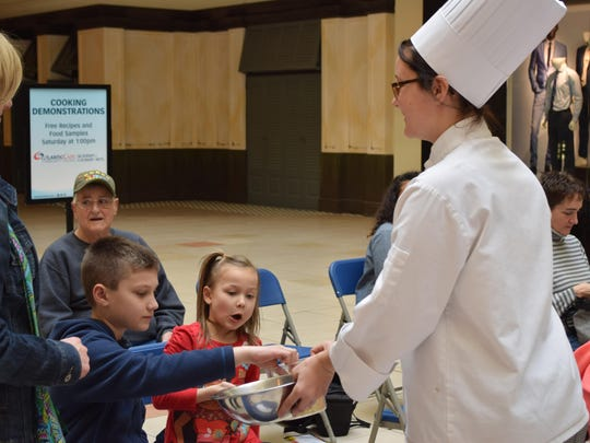 Academy of Culinary Arts student Briana Husak of Vineland offers a taste of chocolate to Matthew Reed, 8, of Egg Harbor Township and Cassidy Friebel, 6, of Cinnaminson.