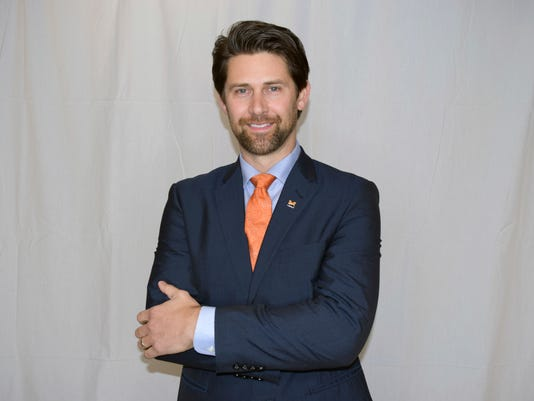 This Feb. 22, 2018, photo provided by Midland University shows Eric Crouch posed at Midland University's Omaha Campus in Omaha, Neb. Crouch, the 2001 Heisman Trophy winner at Nebraska, has been hired as an assistant football coach at Midland University. Midland announced Tuesday, Feb. 27, 2018, that Crouch will coach running backs and special teams. (Tracy Buffington/Midland university via AP)