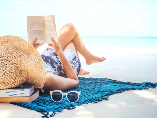 Woman reading a book on the beach in free time summer holiday