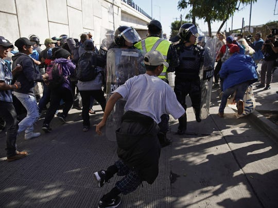 Migrants break past a line of police as they run toward the Chaparral border crossing in Tijuana, Mexico on Sunday near the San Ysidro entry point into the U.S. More than 5,000 migrants are camped in and around a sports complex in Tijuana after making their way through Mexico in recent weeks via caravan.