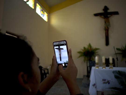 A parishioner makes a photo of the crucifix above the altar at the newly consecrated Sagrado Corazon de Jesus, or Sacred Heart, Catholic church, in Sandino, Cuba, Saturday, Jan. 26, 2019.