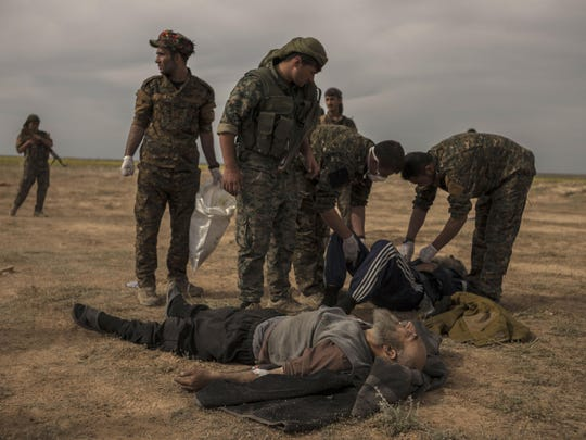 In this March 10, 2019 photo, U.S.-backed Syrian forces stand guard as civilians wounded by airstrikes, during an offensive on the last area held by Islamic State group extremists, are treated at a reception area for evacuees, in Syria's eastern Deir el-Zour province near the Iraqi border, outside of Baghouz, Syria.