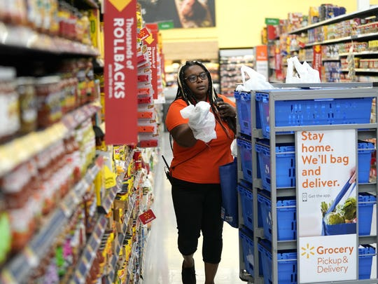 In this Nov. 9, 2018, file photo, Walmart associate Alicia Carter fulfills online grocery orders at a Walmart Supercenter in Houston. More than 40 million individuals receive food stamps in the U.S., according to the USDA.