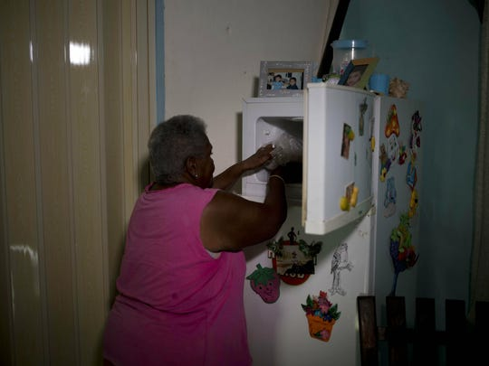 Pura Castell puts in her freezer the three pieces of chicken she received from a government-run Bodega store, as part of her monthly quota of government-distributed food, after failing to find chicken the previous day in Bauta, Cuba, Friday, April 12, 2019.
