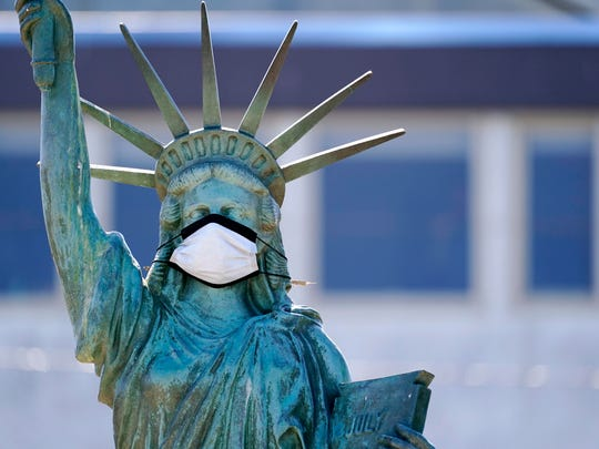 The face on a replica of the Statue of Liberty sports a protective face mask against the coronavirus Wednesday in Seattle. The replica on Alki Beach was erected in 1952 and recast in 2006.