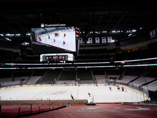 The Philadelphia Flyers play the New Jersey Devils at a nearly empty Prudential Center during the first period of an NHL hockey game in Newark, N.J., on Jan. 26.