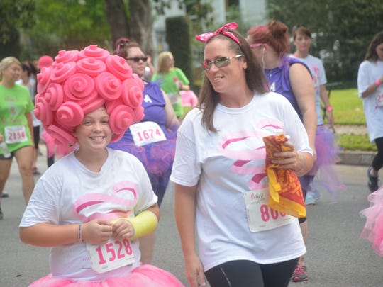 Cendall Barton (left) sports a pink headdress while walking in the 5th annual CenLa Komen Race for the Cure with mom Becky Barton.