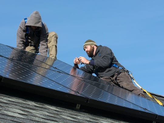 Solar installers from Peck Electric mount the final panel on SunCommon's 1,000th solar home in Barre in December 2014.