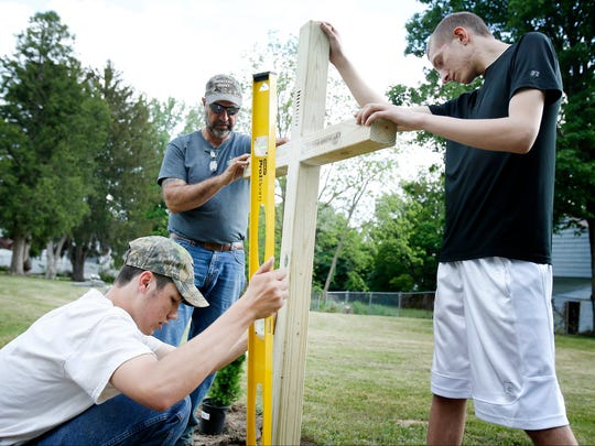 Fifteen-year-old Nathan Burrows, center, levels a cross built by 16-year-old Dustin May, right, as Ed Burrows assists in steadying the cross Wednesday. The cross, which has 56 notches in its center, marks the graves of 56 orphans who were buried in the Fulton Street Cemetery between 1886 to 1942.