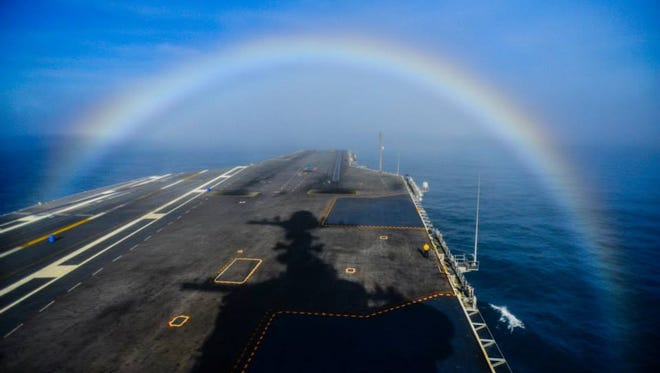 USS John C. Stennis sails under a rainbow on February 3.