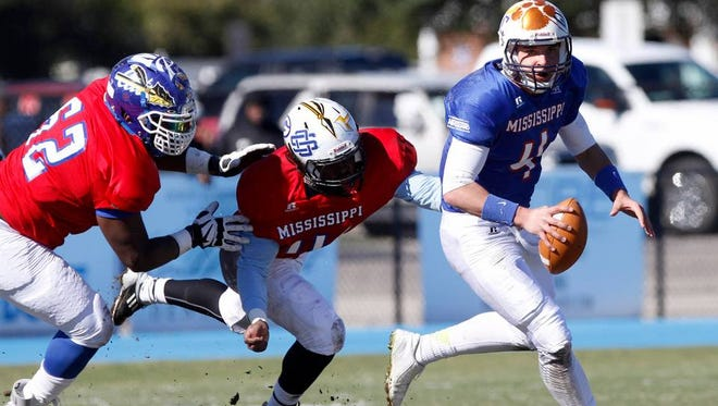 North quarterback Cameron Bowman scrambles away from South defenders Larry Keys and Deontae Haynes Saturday during the Bernard Blackwell All-Star game.