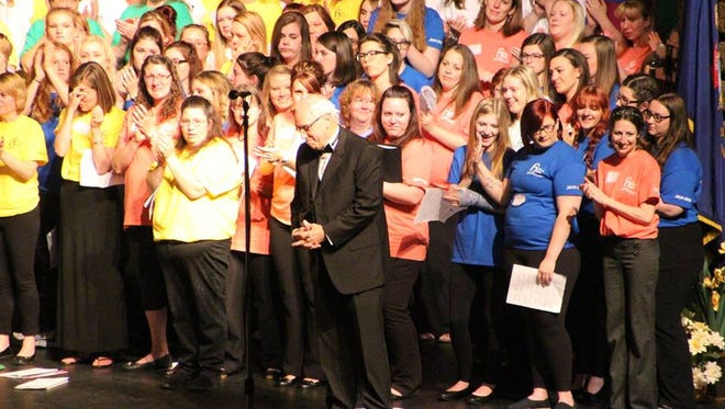 Rod Bushey, front center, takes a moment before giving a speech during the Howell High School Alumni choir concert.