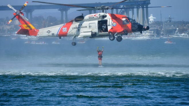 A rescuer leaps from a Coast Guard helicopter.