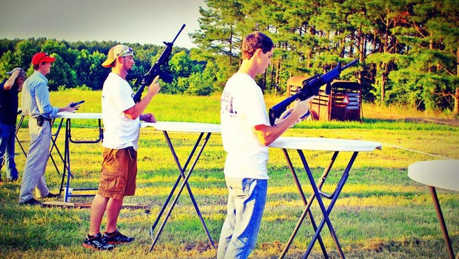 Participants in State Rep. Andy Holt's HogFest and Turkey Shoot load their guns.