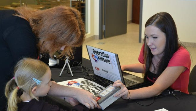 "An operator for Operation Kidsafe uses a Cross Match fingerprint scanner on a little girl's finger at an Operation Kidsafe event. The fingerprint, along with the child's photo, becomes part of a ""bio doc."""