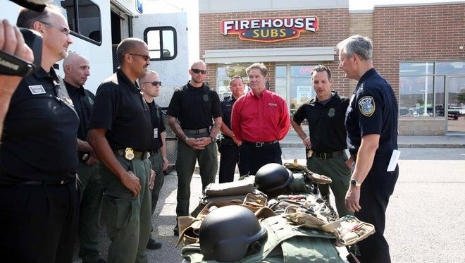 Milwaukee Police Chief Edward Flynn (far right) accepts a donation of bomb squad equipment from Firehouse Subs.