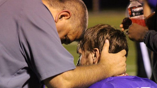 Logansport statistician Tim Wheless shares a moment with Tigers' quarterback Dalton Shaw.