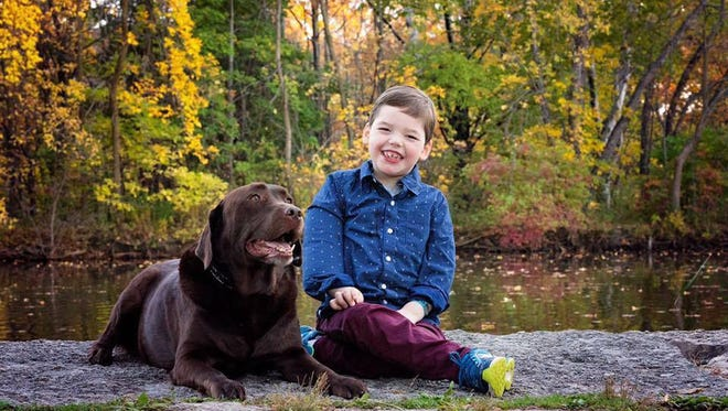"Owen Ostrowski hangs out with Cronkite, a gift from the Make-A-Wish Foundation in 2014. Cronkite is more than just a therapy dog for Owen. ""He and Owen are good buddies,"" Jill Ostrowski said."