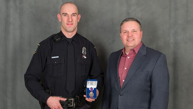 Officer Dustin Meyer is awarded the Sioux Falls Police Department Medal of Valor Award from Police Chief Matt Burns.