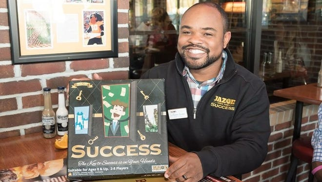 Jason Evans, founder of JAZ-E House Games, with Success, the board game he created.